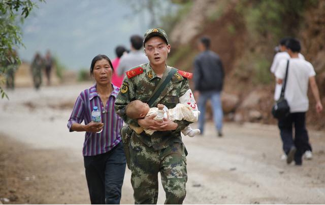 Un rescatista traslada a un bebé después del terremoto.