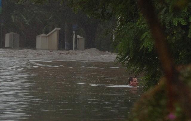 Un hombre intenta salir de la creciente en Villa Allende.